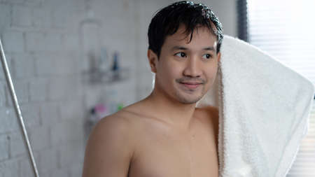 Handsome asian guy wiping  head in the bathroom after  finished shower.