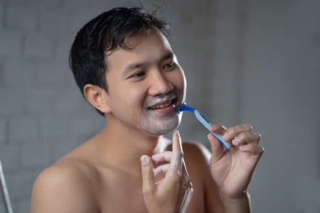 Asian man shaves him looking in the mirror in the bathroom.