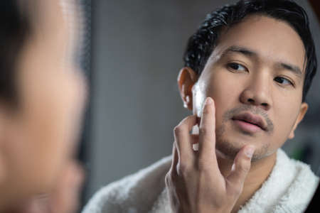 Asian man looking in the mirror at bathroom He touch his face 版權商用圖片