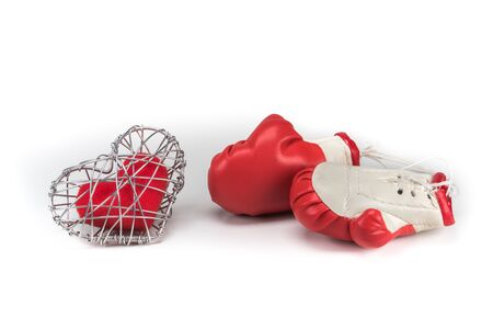 red fabric heart in knitted wire cage on white background
