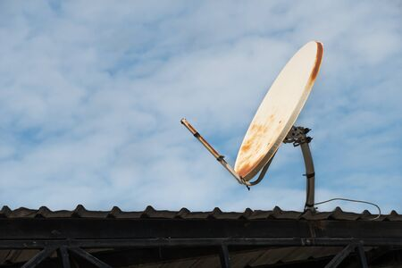 broken and old satellite dish on the roof and blue sky background.