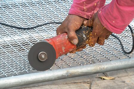 man used angle grinder without cover guard cutting metal net to make bird cage.