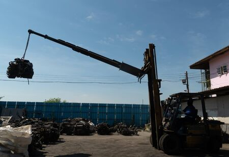 A forklift and workers are lifting an old car's engine for recycling.
