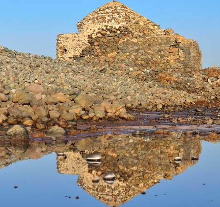 seawater: Old construction reflecting in seawater lagoon