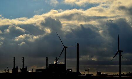 electric power station: Electric power station and wind turbines backlit at dawn Stock Photo