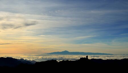 chromatic colour: Vibrant sunset with Roque Nublo in foreground and Tenerife island in background, Canary islands