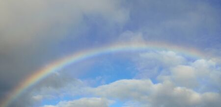 chromatic colour: Colorful rainbow among clouds and blue sky Stock Photo