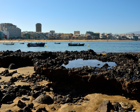 Reef at low tide and blue sky, Las Canteras beach and Las Palmas city, Canary islands