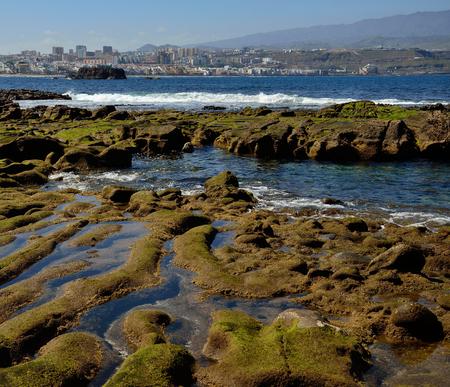 Shoreline at low tide and city, The confital, coast of Las Palmas, Gran Canaria