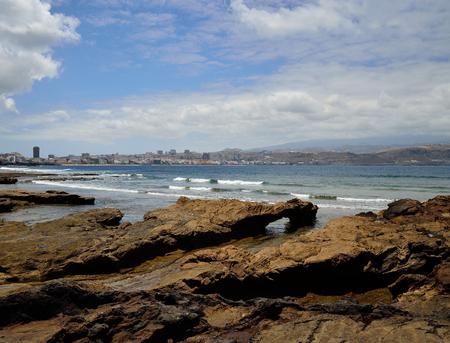 Rocky coast, blue sky, clouds and city, Las Palmas de Gran Canaria, Canary Islands Banque d'images