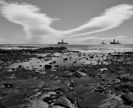 Coast landscape at low tide, oil rigs and cloudy sky, black and white, bay of Las Palmas, Gran Canaria