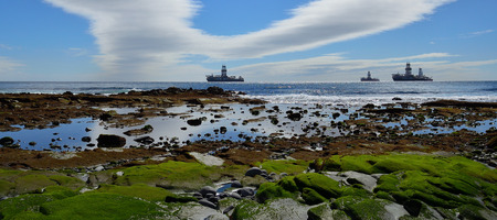 Coast at low tide in foreground, oil platforms in the bay and blue sky with clouds in background