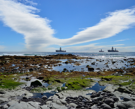 Rocky coast of colors at low tide, blue sky with peculiar cloud and oil rigs, bay of Las Palmas de Gran Canaria