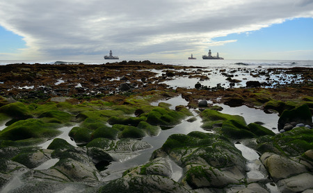 Rocky coast at low tide with small puddles in foreground and oil platforms in the background