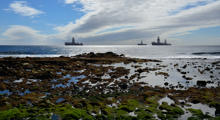 Rocky coast at low tide in foreground, cloudy sky and oil platforms in the background