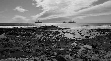 Rocky coast at low tide, oil platforms and cloudy sky, black and white mode Imagens