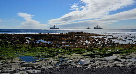 Rocky beach at low tide and oil platforms in the bay, coast of Las Palmas, Gran Canaria Imagens