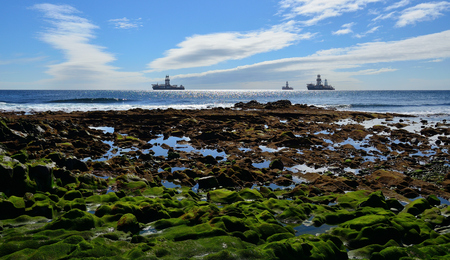 Rocky coast at low tide with many puddles, blue sky, clouds and oil platforms in the bay