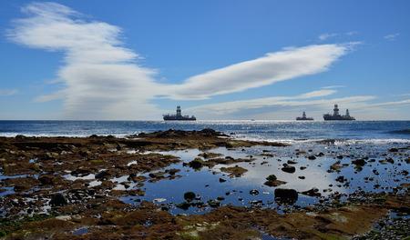 Coast at low tide, oil platforms and blue sky with peculiar clouds, bay of Las Palmas de Gran Canaria Imagens