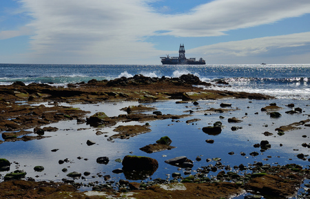 Coast with large puddle at low tide and oil rig in the background