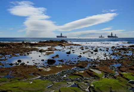 Coast of colors at low tide, oil rigs and blue sky with peculiar clouds, bay of Las Palmas de Gran Canaria Imagens