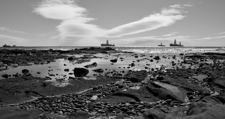 Rocky beach at low tide and ships in the bay, coast of Las Palmas, Gran Canaria, black and white