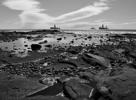 Rocky coast with puddles at low tide and oil rigs in the bay, black and white, Gran Canaria