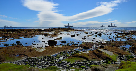 Rocky beach at low tide, ships and blue sky with clouds, coast of San Cristobal, Gran Canaria, Spain