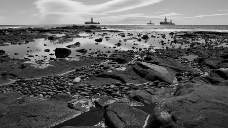 Rocky beach at low tide and oil rigs, bay of Las Palmas de Gran Canaria, monochrome mode, Canary Islands