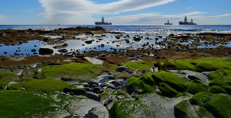Coast at low tide in foreground, calm sea, blue sky with clouds and oil rigs in the bay Imagens
