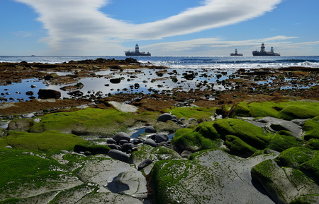 Coast landscape at low tide with oil rigs in the bay and blue sky with clouds Imagens