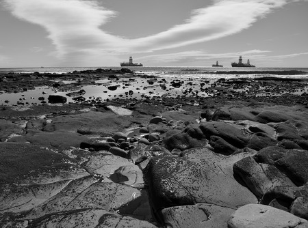 Rocky coast at low tide in foreground and oil rigs in the background, monochrome effect