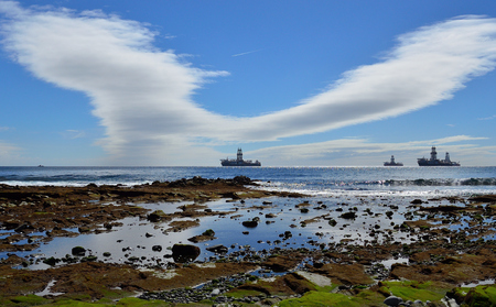 Coast landscape at low tide, oil rigs and blue sky with peculiar cloud, bay of Las Palmas, Gran Canaria