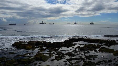 Rocky coast with calm sea, cloudy sky and ships anchored in the bay Imagens
