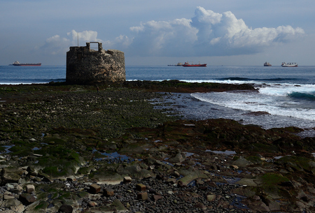 Old defensive tower, low tide and ships in the background, bay of Las Palmas de Gran Canaria