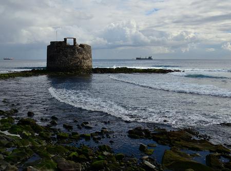 Old defensive tower by the sea, bay of Las Palmas de Gran Canaria, Canary Islands Editorial