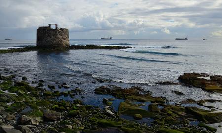 Coast at low tide and old defense tower, San Cristobal, bay of Las Palmas de Gran Canaria