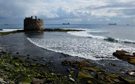 Coast at low tide and old defense tower, bay of Las Palmas de Gran Canaria Editorial