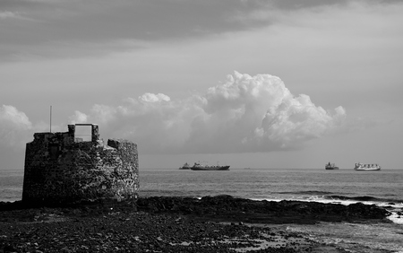 Old defense tower by the coast and ships in the bay, San Cristobal, Gran Canaria