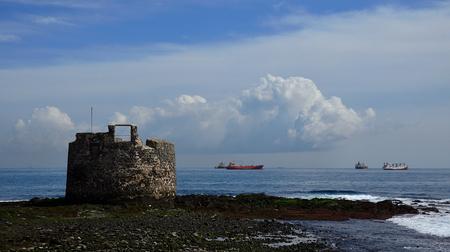 Old defense tower by the sea and ships in the bay, Las Palmas de Gran Canaria