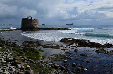 Coast at low tide and old defense tower by the sea, San Cristobal, Gran Canaria
