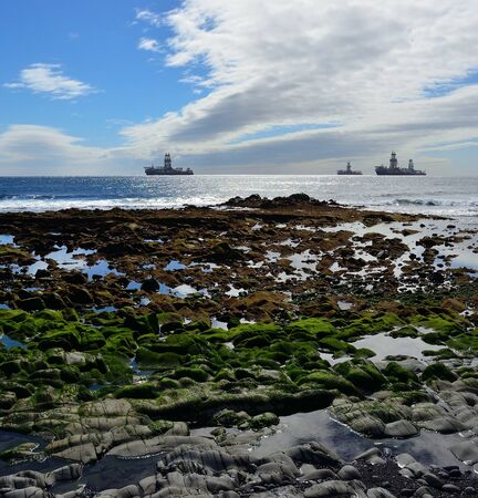 Rocky beach with many water puddles at low tide and ships anchored in the bay