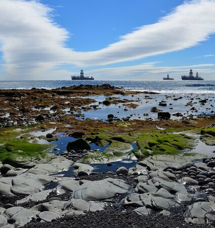 Rocky beach at low tide, blue sky with singular cloud and ships in the bay, coast of Las Palmas de Gran Canaria