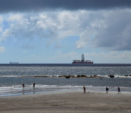 Sandy beach at low tide and people walking on the shore, cloudy sky and ships, coast of La laja, Las Palmas de Gran Canaria
