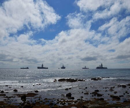 Coast at low tide with stones in foreground, blue sky with clouds and ships anchored in the bay