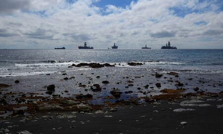 Sand and stones beach at low tide, calm sea with ships anchored in the bay and cloudy sky