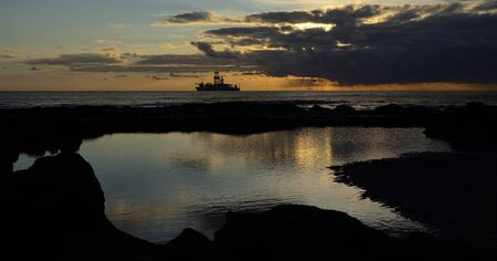 Natural pool between the rocks with low tide at sunrise, ship and cloudy sky