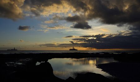 Beautiful sunrise with blue sky and clouds, natural pool and ships, La Laja, coast of Las Palmas, Gran Canaria