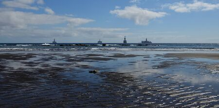 Sandy beach with puddles at low tide and ships in the background, La Laja, Gran Canaria