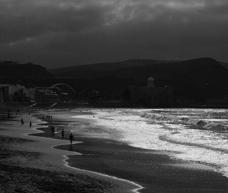 Plage avec des passants au coucher du soleil, Las Canteras, Las Palmas de Gran Canaria, Espagne, effet monochrome
